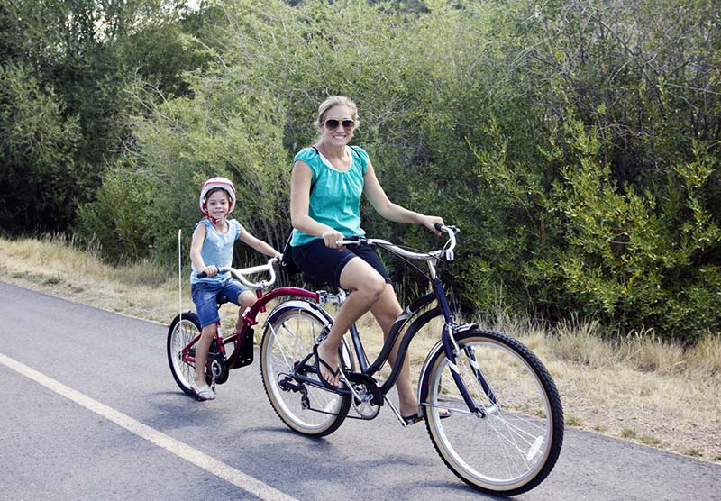mom and son riding on tandem bike with tree landscape in background