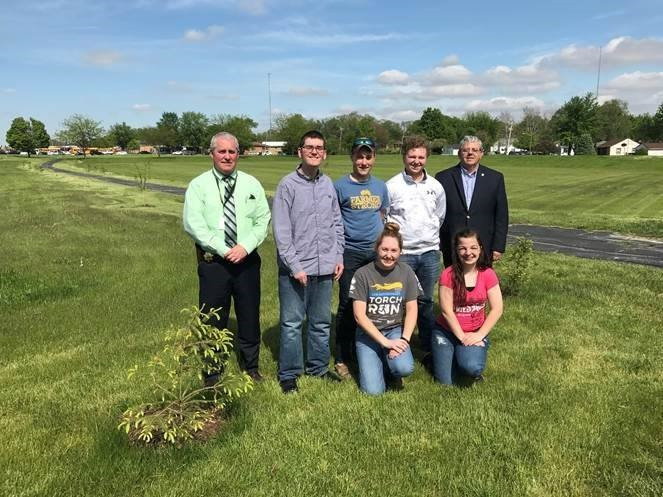 Police Chief Jim Phelps, Mayor Paul Schore, and five bradley-bourbonnais community high school students in park field where trees were planted